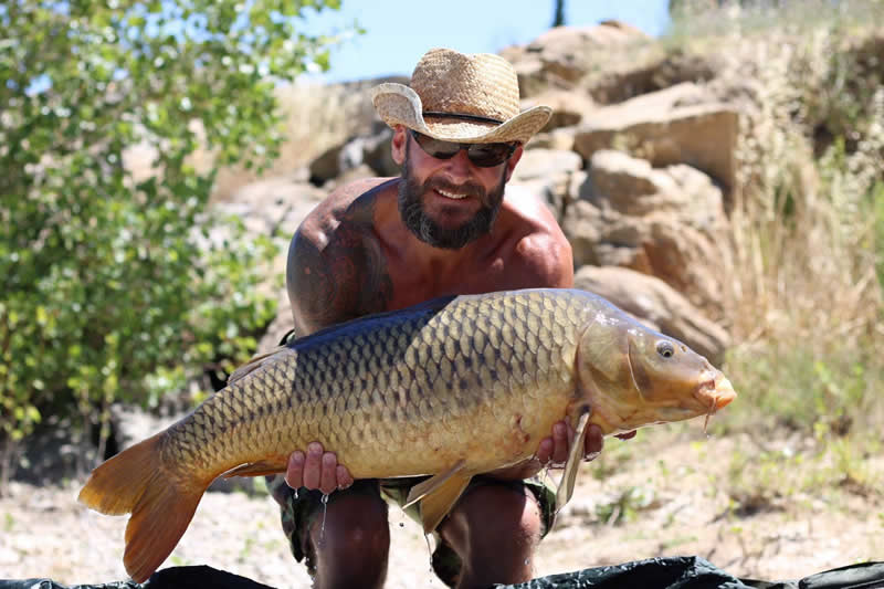 Man with hat holding carp